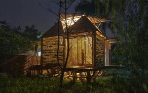 Casa de bambú iluminada en la noche